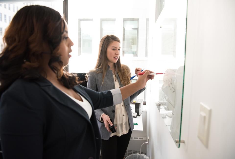 Deux jeunes femmes travaillant ensemble sur un tableau blanc
